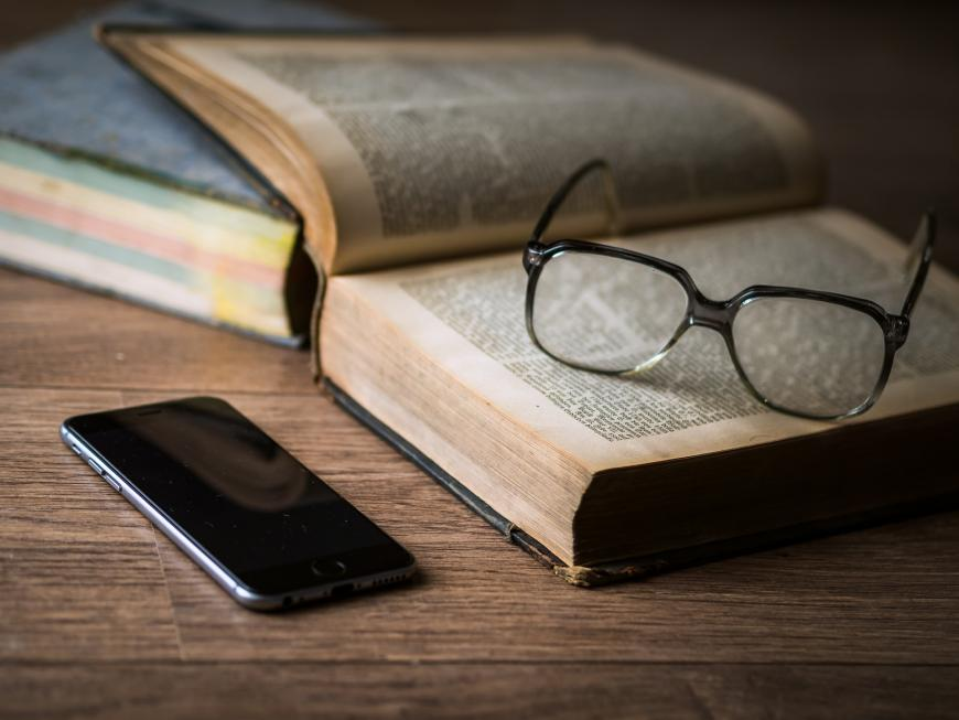 Smartphone, glasses, and books on a desk