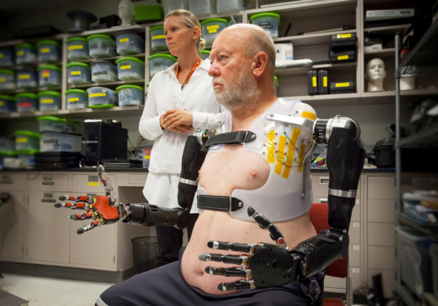 Man wears prosthetic arms with jointed fingers as researcher looks on.