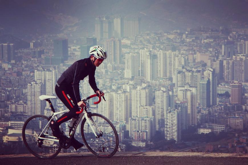 Cyclist riding on a hill above a smoggy metropolitan city