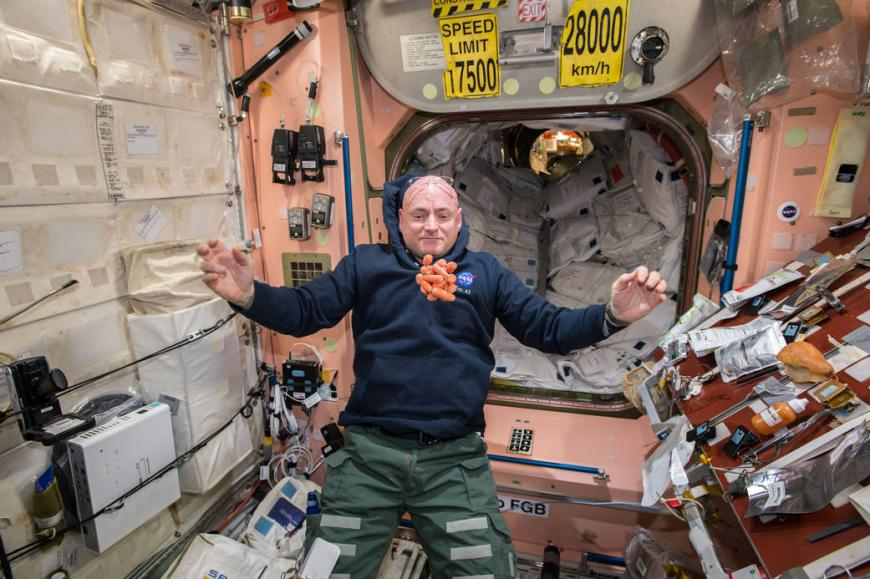 Astronaut Scott Kelly eyes a ball of carrots floating in front of him