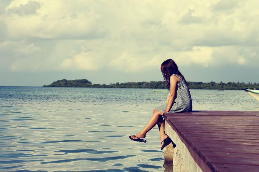 Girl sitting on a dock on the lake