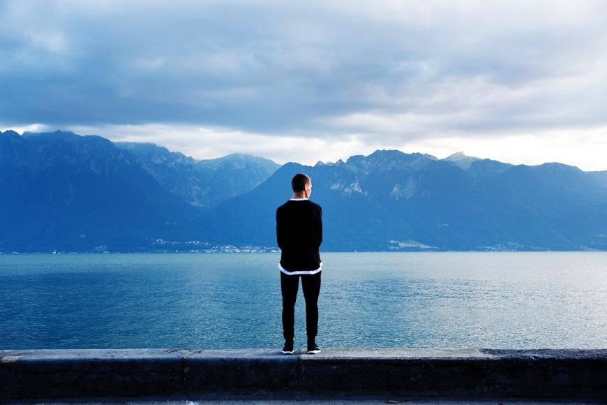 man alone on the edge of a lake