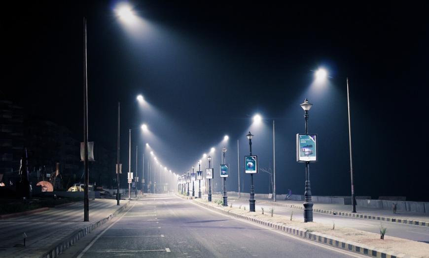 Streetlights illuminate an empty road at night