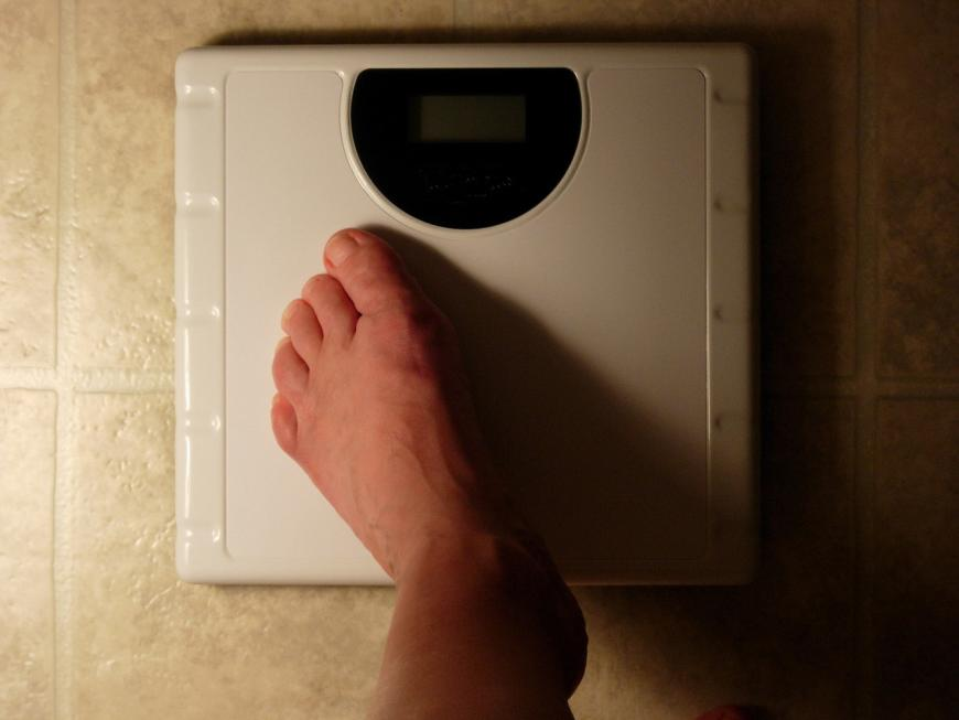Foot on a scale. Weight.