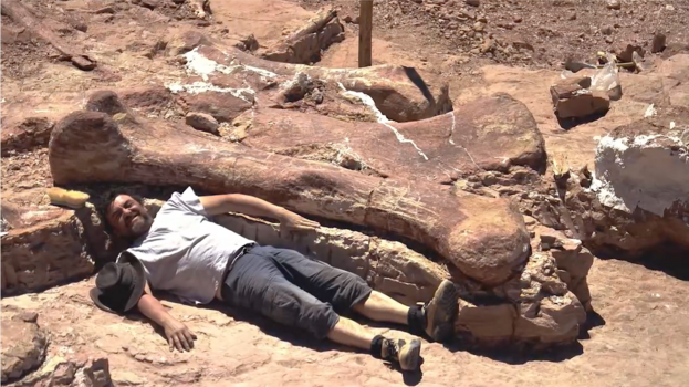Man lying next to a dinosaur bone that is much longer than he is