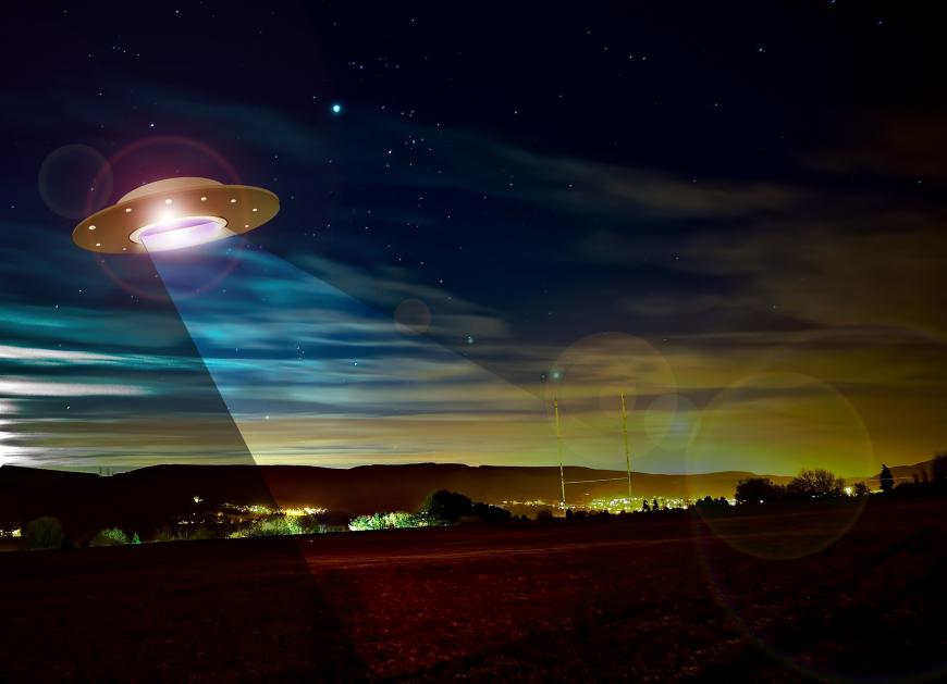 computer generated image of a cartoon UFO beaming light on a city