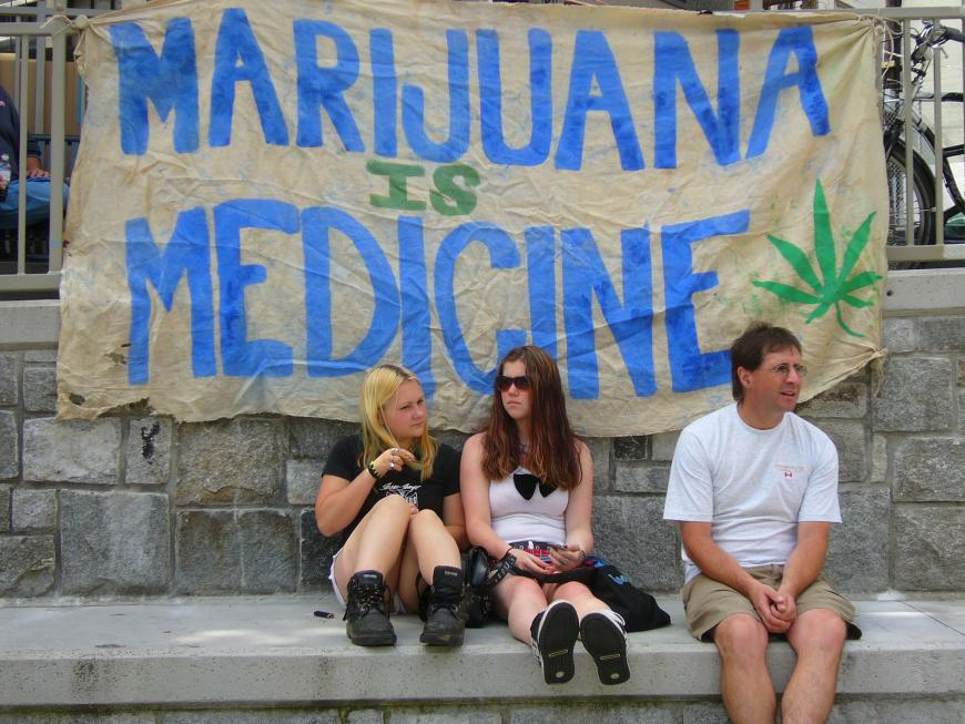 """People sit on a sidewalk in front of a sign reading """"Marijuana is Medicine."""""""
