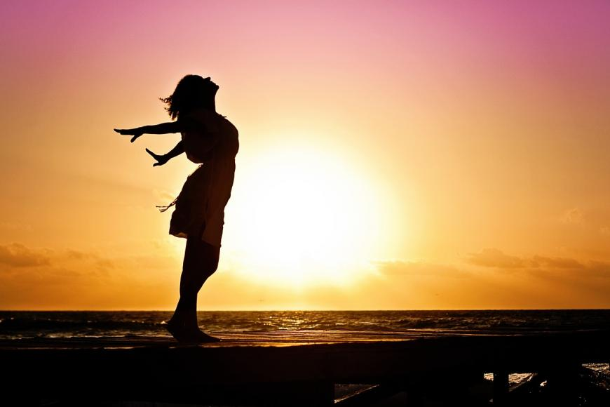 woman posing in front of a sunrise