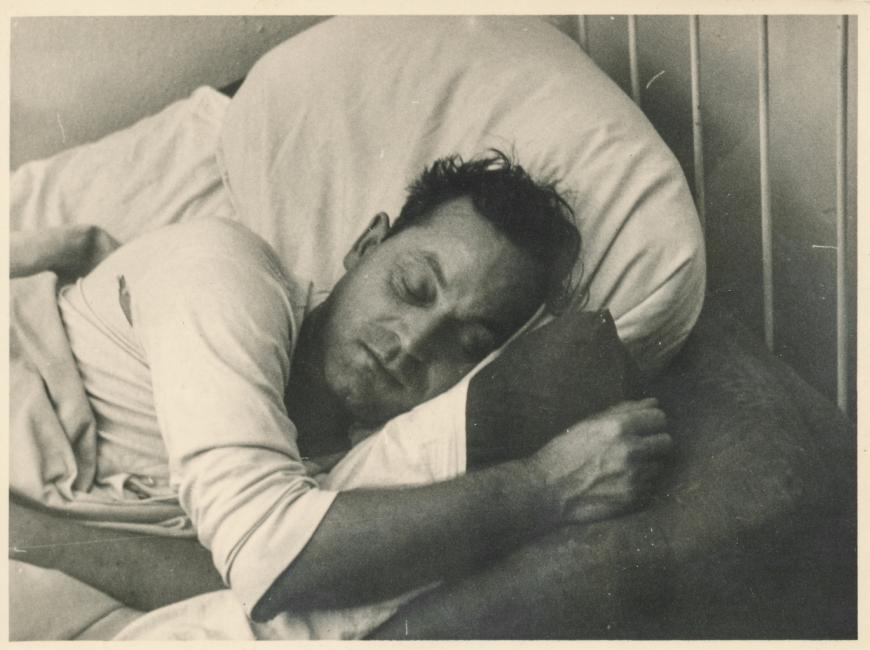 Old black and white photo of a man sleeping in bed