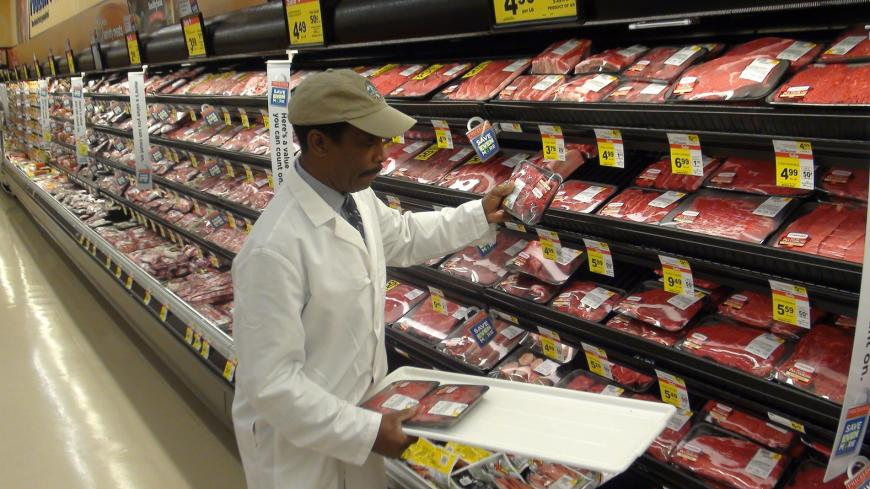 Grocery store employee restocking shelves in the meat aisle