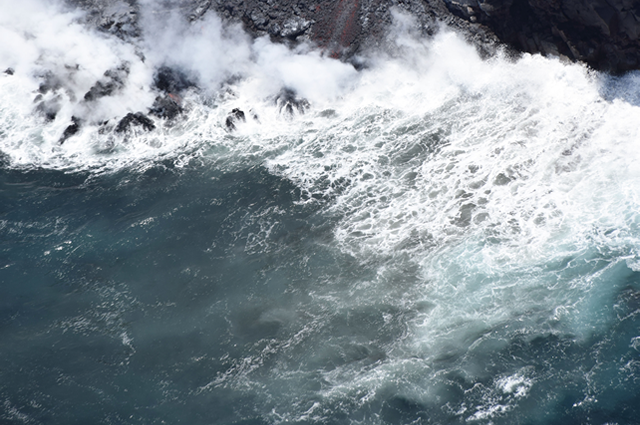 Lava from Hawaii's Kilauea volcano spills over a cliff into the ocean