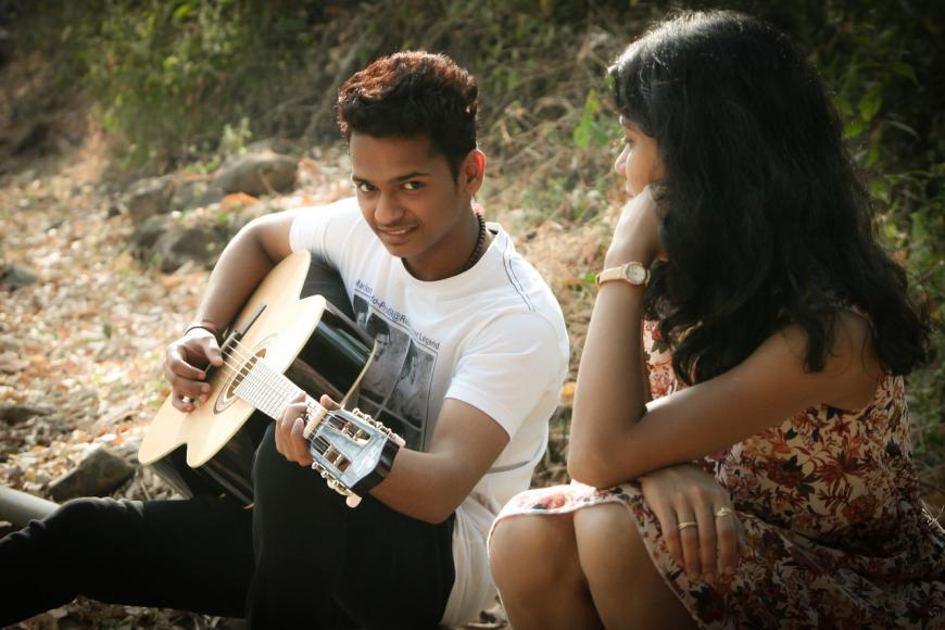 Young man serenading a woman on guitar. Couple