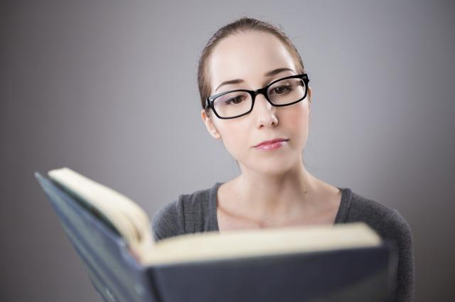woman in glasses reading a book