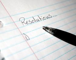 """a piece of lined paper and a pen. The word """"Resolutions"""" with a listed below"""