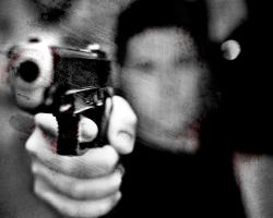 Heavily filtered black and white, blood-splattered image of a man pointing a gun at the camera.
