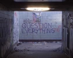 """Graffiti in a subway entrance reads """"Question Everything"""""""