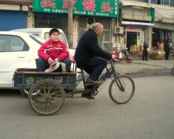 Chinese boy lets grandfather pull him in a cart