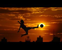 Football (soccer) silhouette against sunset.