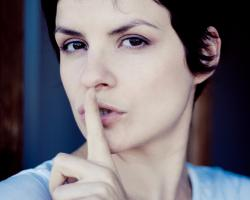 Woman with her finger in front of her lips. Shhhhh