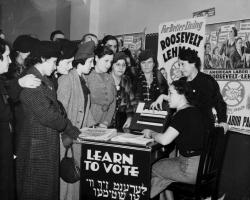 Women surrounded by political posters, learning how to vote in 1935