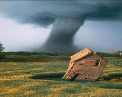 A tornado in the background. In the foreground an old wooden house tilts over in the wind.
