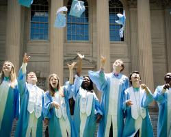 Students throw their caps in the air after graduating
