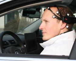 photograph of a man in the driver's seat of a car wearing an elaborate headset.