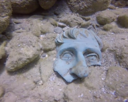 Fragment of a bronze mask on the seafloor