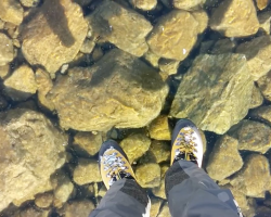 A photograph of a man's feet standing on a crystal clear frozen lake. The rocks are visible below.