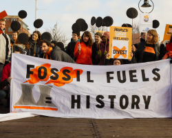 "Protesters with banner reading ""Fossil Fuels = History"""