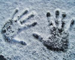 Two handprints on a frosty, snow-covered surface