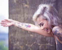 Young woman with tattoos, laughing