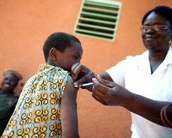 A child receives an injection to his shoulder