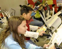 Students read while pedalling exercise bikes