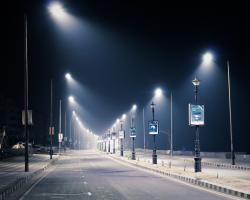 Streetlights illuminate an empty road at night