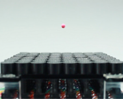 a small red ball levitates over a flat field of black speakers