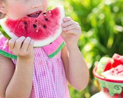 Young girl eating watermelon on a summer day